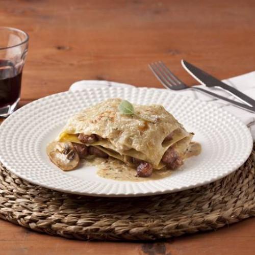 Lasaña fácil con espinacas, salchichas, cebolla confitada y setas