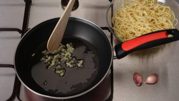 Hierve los espaguetis tal como se indica en el envase.  Escurre y rocíalos con un poco de aceite. Mientras, sofríe los ajos en una sartén con seis cucharadas de aceite.