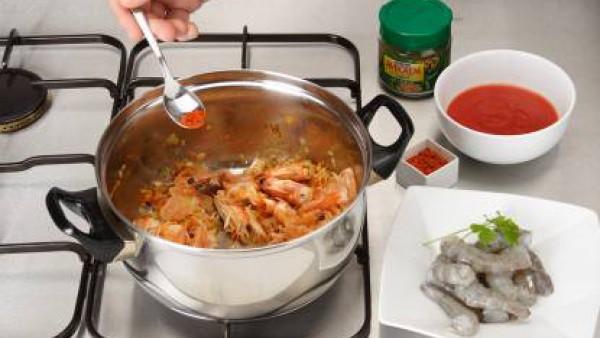 Pelar los langostinos y reservar a parte. Sofreír las cáscaras con aceite en la olla, junto con las verduras picaditas, y cuando estén tiernas y doradas, añadir el pimentón, el Tomate Frito Gallina Bl