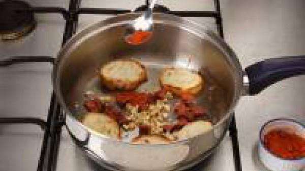 En una cazuela, rehoga los ajos.  Cuando estén dorados, sofríe el chorizo y el pan cortado a rebanaditas, dándole la vuelta para evitar que se quemen.  Espolvorea por encima el pimentón.