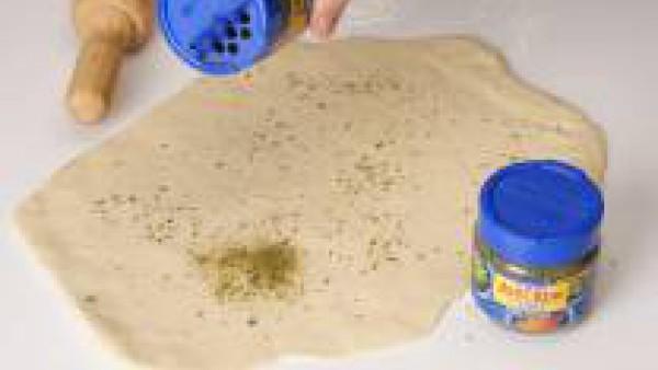 Mezclar los ingredientes para formar la masa. Estirarla y darle forma redonda. Espolvorearla con Avecrem Caldo de Pollo Granulado y condimento de finas hierbas.