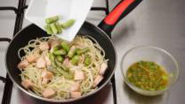Saltea los espaguetis con un poco de aceite, añade el salmón y las puntas de los espárragos