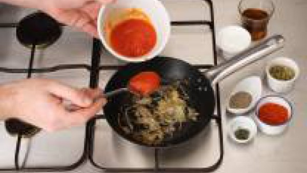 Rehoga la cebolla, incorpora el Tomate Frito Gallina Blanca y la pizca de azúcar, remueve bien. Incorpora el coñac y deja evaporar. Añade la mezcla de hierbas: orégano, canela, pimienta molida, tomill
