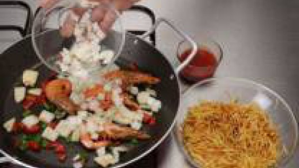 En la misma paellera, saltea la sepia troceada, junto con el pimiento verde i el bote de sofrito de hortalizas, sazona con Avecrem Pescado -30% de Sal. Añade un poco de Caldo para Fideuá Fácil 100% Na
