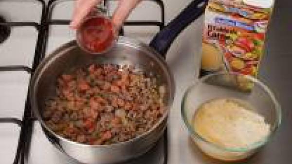 Incorpora el foiegras, el extracto de tomate, la miga de pan y 25 g de queso parmesano.