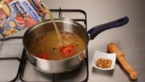 Agrega el caldo. Aparte, prepara una mezcla con los ajos, las almendras picadas, el azafrán y unas gotas de licor.