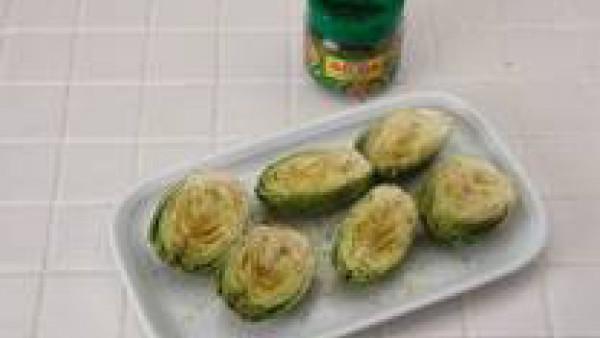 Parte en dos trozos las alcachofas y ponlas en la bandeja de horno con un poco de aceite por debajo y por arriba.