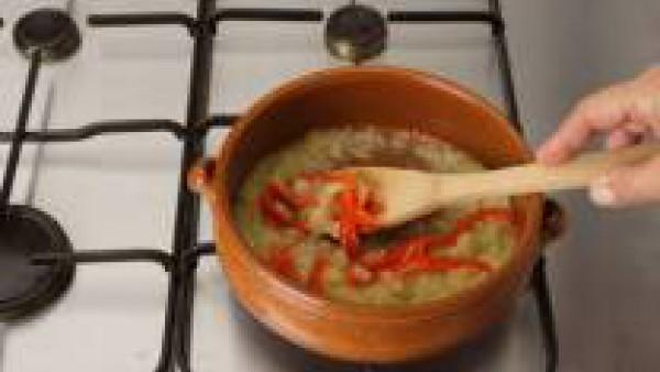 Pica los embutidos en dados, saltea en aceite en una cazuela y retira. Saltea el pimiento y el sofrito de cebolla. Rehoga el arroz y añade al caldo, después de cocer los huesos de jamón dentro.