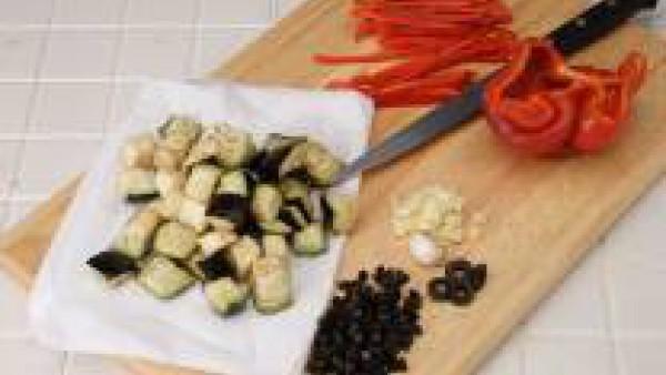 Pela las berenjenas y córtalas a dados. Ponlas en un colador con sal gorda durante 30 minutos. Acláralas con agua fría, escúrrelas y sécalas muy bien con papel absorbente.