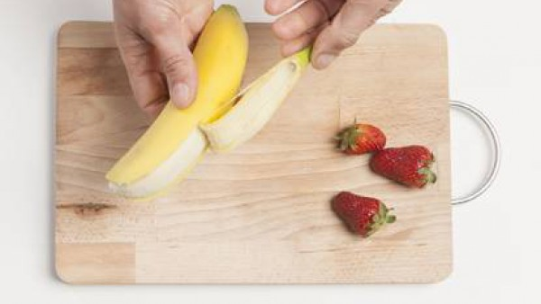 Pela todas las frutas y córtalas a gajos.  Limpia las fresas.