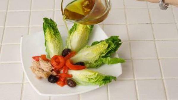 Monta los platos poniendo los cogollos con el atún, las tiras de pimiento y las aceitunas por encima. Riega con el aliño cuando todavía esté templado y sirve.