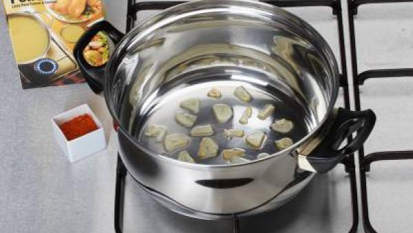 En una sartén, calienta un poco de aceite y unos ajos fileteados, rehoga y echa por encima de la merluza.
