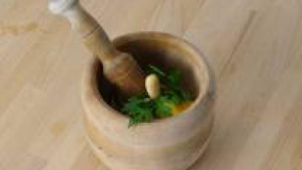 Aparte, en un mortero, machaca las almendras con la yema cocida, sal gorda y perejil. Vierte este majado a la cazuela para engordar la salsa.