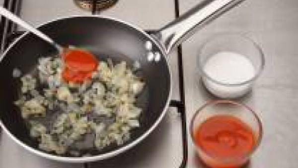 En el mismo aceite sofríe el ajo, el pimiento verde y el pimiento rojo. Cuando esté doradito, agrega el sofrito y añade el azúcar y el zumo de limón. Remueve y deja cocer durante unos 10 minutos.
