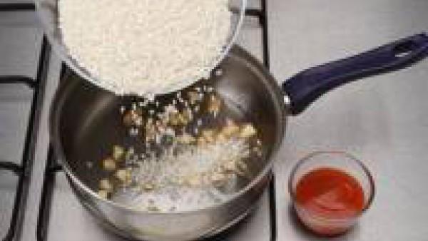 Pon el aceite a calentar. Después, incorpora los ajos pelados y cortados a trocitos pequeños. Cuando empiecen a tomar color, añade el arroz y la salsa de Tomate Frito Gallina Blanca.