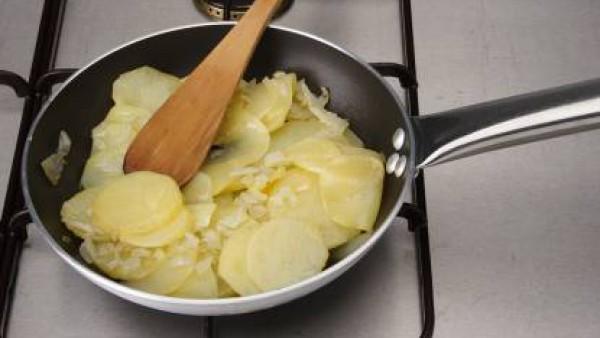 Pela las patatas y córtalas redondas. Corta la cebolla y los pimientos en cuadritos.  Fríe todo en una sartén con aceite de oliva. Cuando esté a medio freír, pon las patatas y fríelas hasta que estén