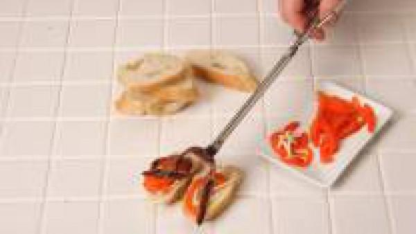 Coloca sobre el pan las tiras de pimiento y adorna estas con las anchoas. Sirve.