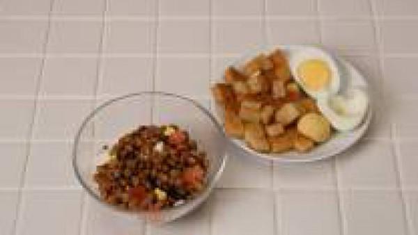 Mezcla las lentejas con el queso, el tomate y el huevo duro. Alíñalo con la vinagreta y sírvalo con pan frito cortado en dados.