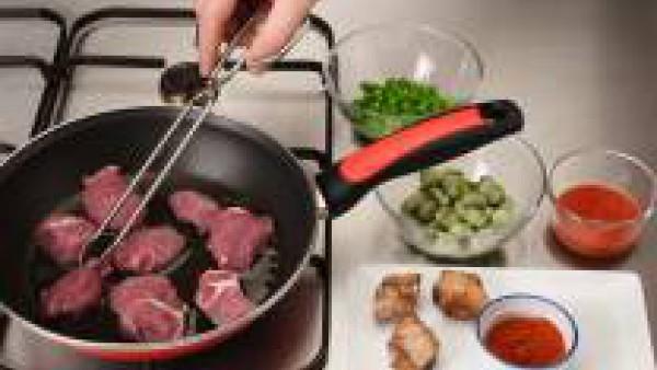 Rehoga en aceite caliente la carne magra y las costillas. Añade las habitas, los guisantes, los ajos partidos a trozos, el tomate frito y media cucharadita de pimentón. Agrega el arroz y sofríe un poc