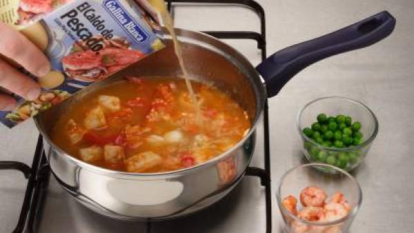 Riega con el caldo de pescado, deja cocer durante 10 minutos. Añade, por último, las gambas sin descongelar y los guisantes. Condimenta con el azafrán y deja cocer durante 8 minutos más. Sirve calient
