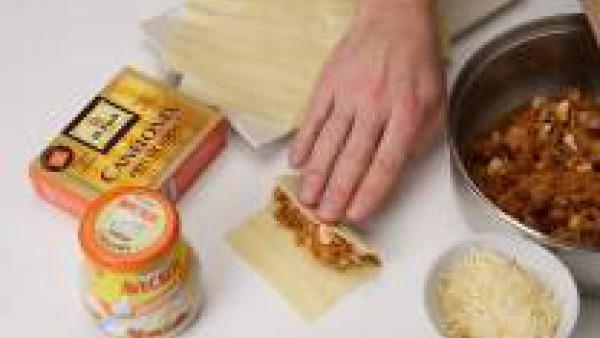 Reparte el preparado sobre los canelones y enrolla. Pon un poco de Tomate Frito en Trozos en el fondo de una fuente para horno y dispón encima los canelones.