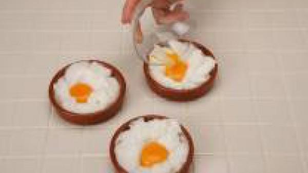 Untar con mantequilla 4 cazuelitas y poner en cada una la cuarte parte de las claras montadas