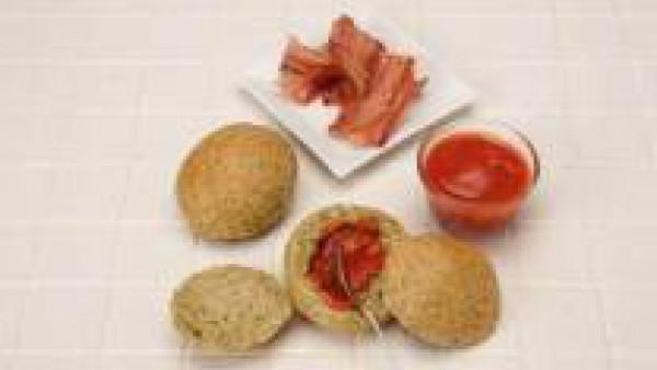 Abre los panecillos por la mitad y quítales un poco de la miga. Reparte por encima unas 6 cucharadas de tomate frito caliente. Dora las lonchas de bacón, pártelas por la mitad y ponlas de dos en dos s