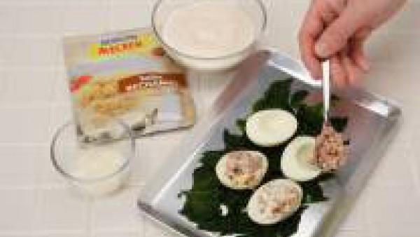 Prepara la Salsa Bechamel con la leche y siguiendo las instrucciones del sobre. En una fuente de horno, pon las espinacas en el fondo y los huevos encima. Cubre con la Salsa bechamel y el queso rallad