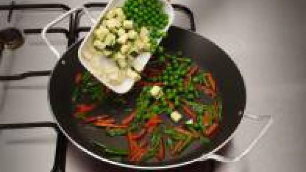 Incorpora el calabacín a dados, los guisantes y los ajos laminados.