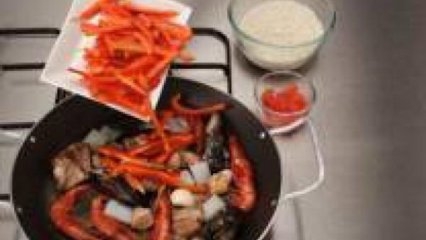 Añadir el pimiento a tiras y el ajo, remover y agregar el arroz. Si se quiere, poner un poco de colorante.
