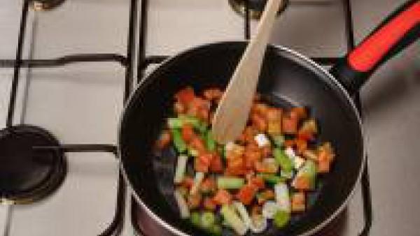 Fríe los ajos tiernos en el aceite caliente y añade el arroz, deja que se dore ligeramente. Añade el tomate frito.