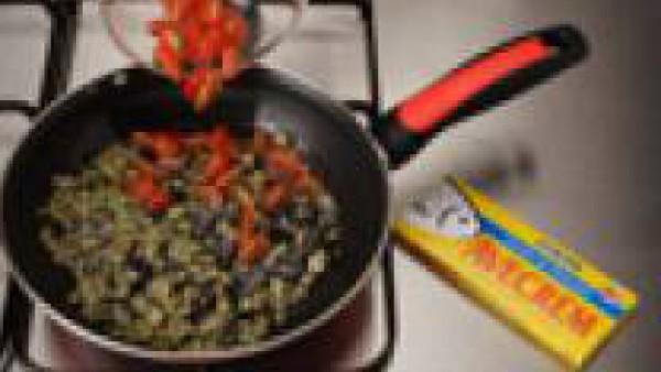 Pela la berenjena y déjala en remojo en abundante agua con sal durante unos minutos. Lávala, córtala en dados muy pequeños y fríela en una sartén con el aceite de oliva durante 5 minutos hasta que est