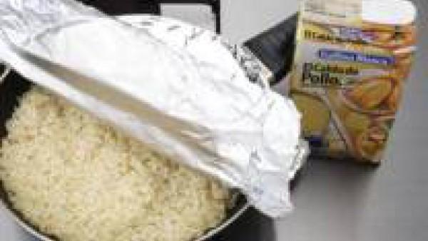 Rehoga el arroz con los ajos en el aceite caliente e incorpora el Caldo Casero de Pollo 100% Natural Gallina Blanca
