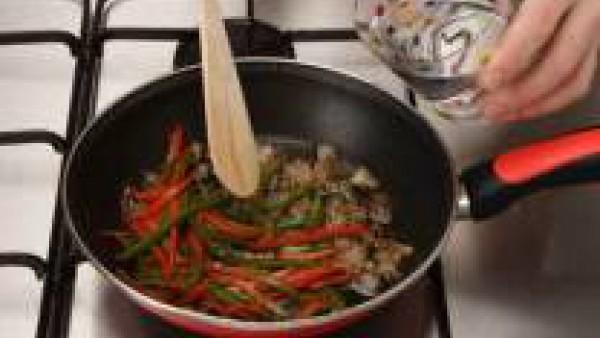 Lava los pimientos y córtalos en tiras finas. Pela la cebolla, trocéala y dórala en una sartén con el aceite. Añade los pimientos, tapa y rehoga a fuego lento durante 15 min. Añade un poco de agua si