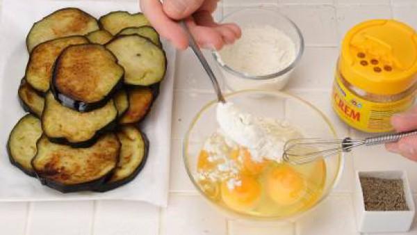 Corta las berenjenas a rodajas gruesas y fríelas. Réservalas sobre papel de cocina. Bate los huevos junto con la harina y sazonálos con Avecrem Caldo de Pollo y pimienta.