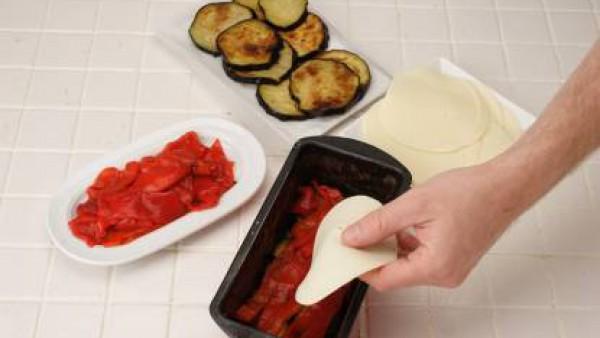 Corta a tiras los pimientos asados. Engrasa un molde de pastel y alterna en capas las rodajas de berenjena, pimiento y lonchas de queso sin llenar el molde.