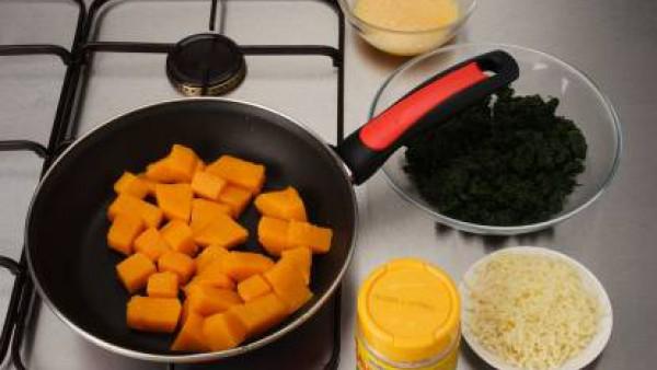 Pela la calabaza, quita las semillas y corta en dados. Cuece las espinacas. Pela y pica la cebolla y saltéala en el aceite. Escurre las espinacas, pícalas y saltéalas. Aparta. Añade la calabaza y deja