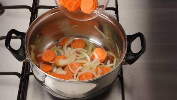 Rehoga el sofrito de cebolla y añade las zanahorias a ruedas. Mantén tapado a fuego lento 5 -6 min.