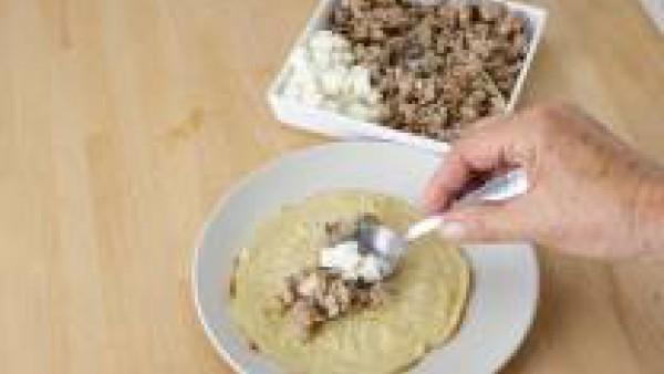 Pon un montoncito de la mezcla de carne y queso en el centro de cada crepe y enróllalas. Coloca en el plato de servir y decóralo con perejil.