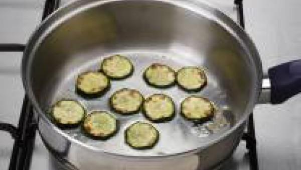 Pon a calentar en una cazuela unas cucharadas de aceite y los calabacines cortados a ruedas finas.