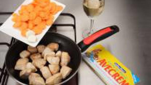 Sazona el pavo con el Avecrem Caldo de Pollo, enharínalo y dóralo en aceite. Añade los ajos enteros, las zanahorias cortadas a rodajas finas y el vino blanco. Deja que evapore.