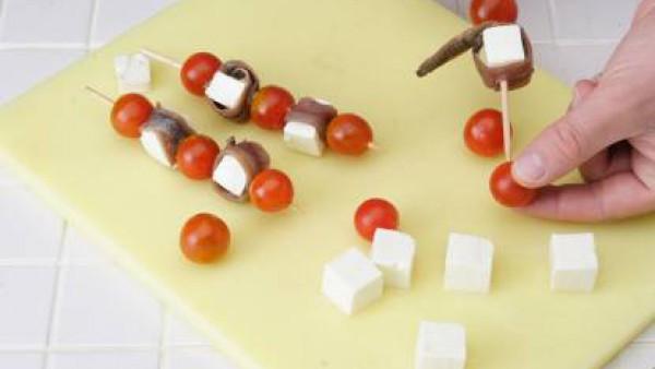 Inserta un tomate y un taco de queso con una anchoa a su alrededor y tepite la operación tantas veces como sea necesario. Se finaliza la brocheta con otro tomate Cherry.
