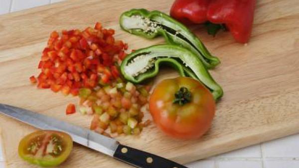 Lava los pimientos y los tomates. Ábrelos y quitarles las semillas. Córtalos todos en daditos muy pequeños.