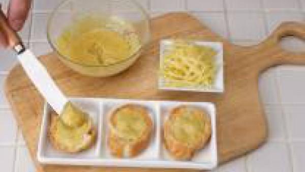 Extiende la mantequilla preparada sobre las tostadas y ralla abundante queso por encima
