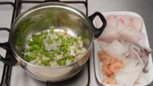 Limpia el pescado y el marisco.  En una cazuela rehoga en aceite la cebolla, el ajo y el pimiento picados muy finos. Cuando ya se están dorando, añade el pescado troceado y deja sofreír un poco.