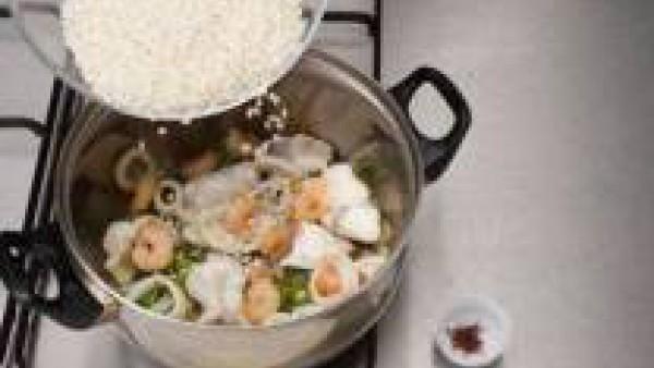 Agrega el arroz, rehoga y echa el azafrán, el caldo bien caliente y los guisantes. Después de unos 10 minutos, incorpora las almejas y deja cocer otros 10 minutos más. (Tiene que quedar un poco caldos