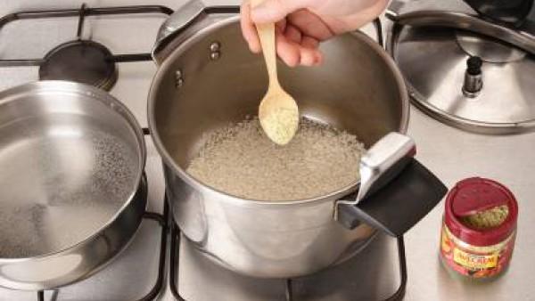 Pon un poquito de aceite en la olla rápida, rehoga el arroz con el sazonador Avecrem. Riega con el agua caliente.