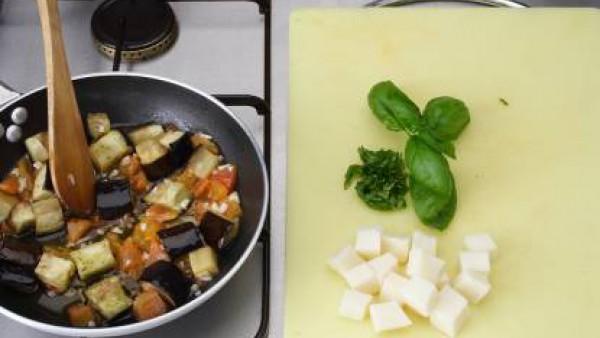Lava la berenjena y, sin pelarla, córtala en taquitos. Espolvorea con sal y déjala reposar durante un mínimo de 20 minutos.  Aclarala bien y sécala.  Pela y trocea los tomates. Lava y secar la albahac
