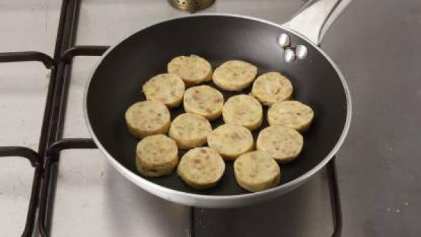 Corta la butifarra en rodajas de 1 cm aproximadamente y saca la piel. Fríe ligeramente las rodajas en aceite.
