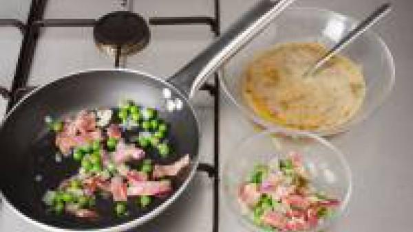 En la misma sartén caliente, con media cuchara de aceite y una cuarta parte de los guisantes salteados, vierte una cuarta parte del huevo batido.  Cubre con una tapa y deja cuajar unos minutos sin dar